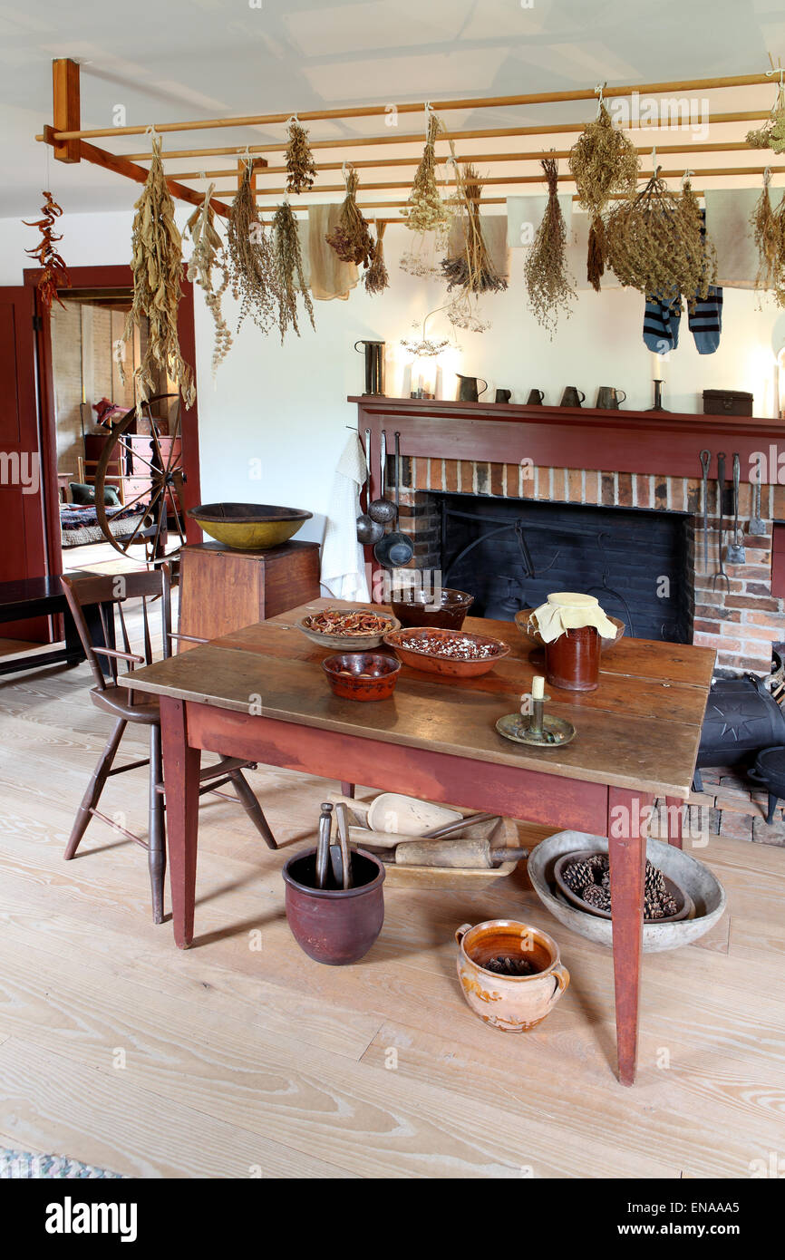 A dining room and fireplace in a primitive colonial style reproduction home.This home is a museum, and filled with - Stock Image