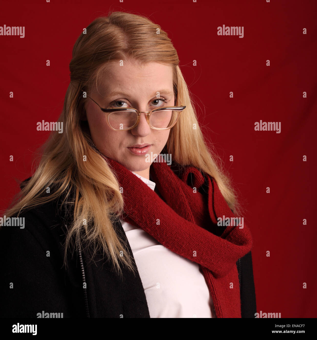 Beautiful young woman in coat and scarf at a 1960's retro student. - Stock Image