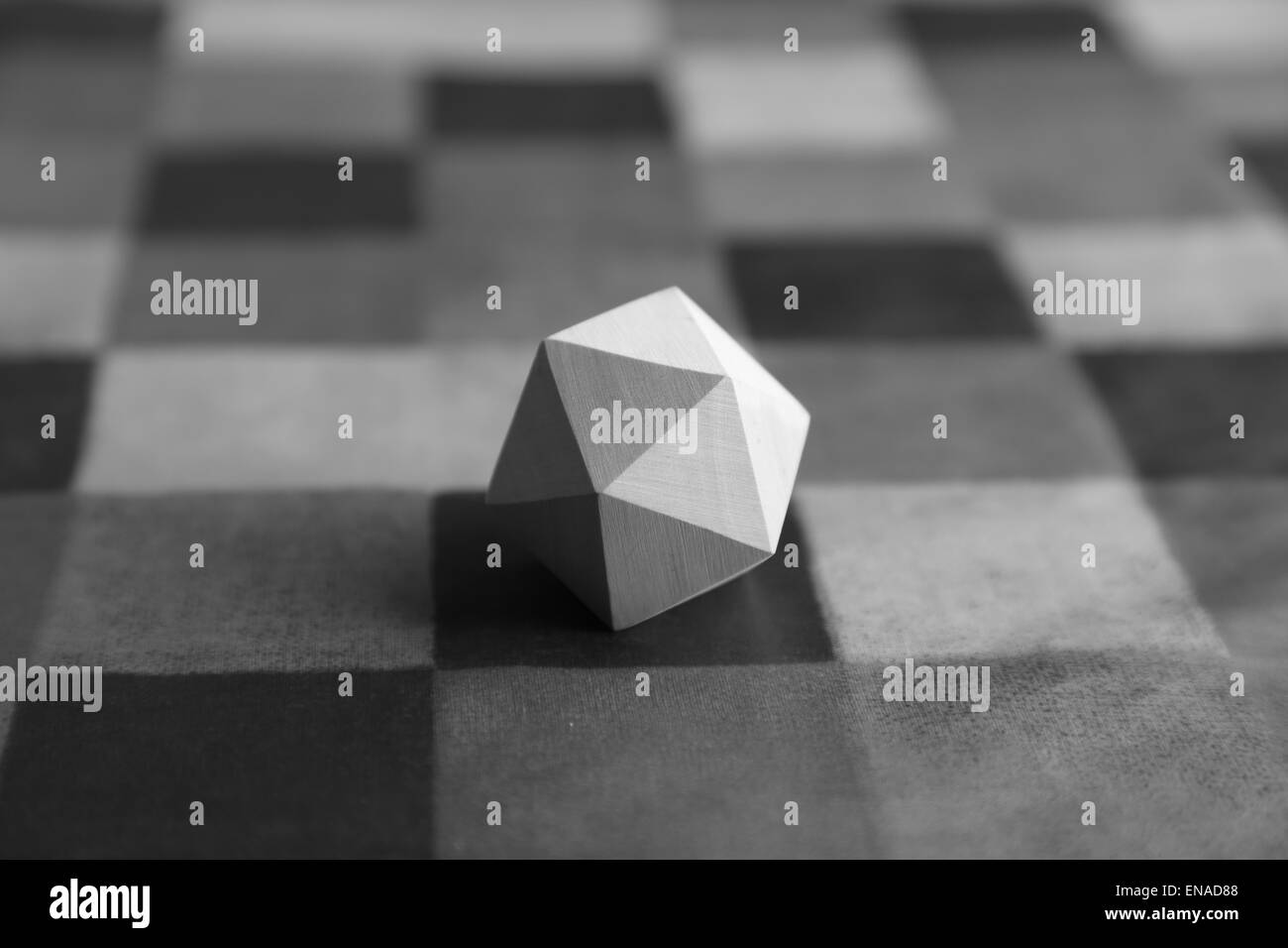 A wooden, regular icosahedron resting on a patterned surface - Stock Image