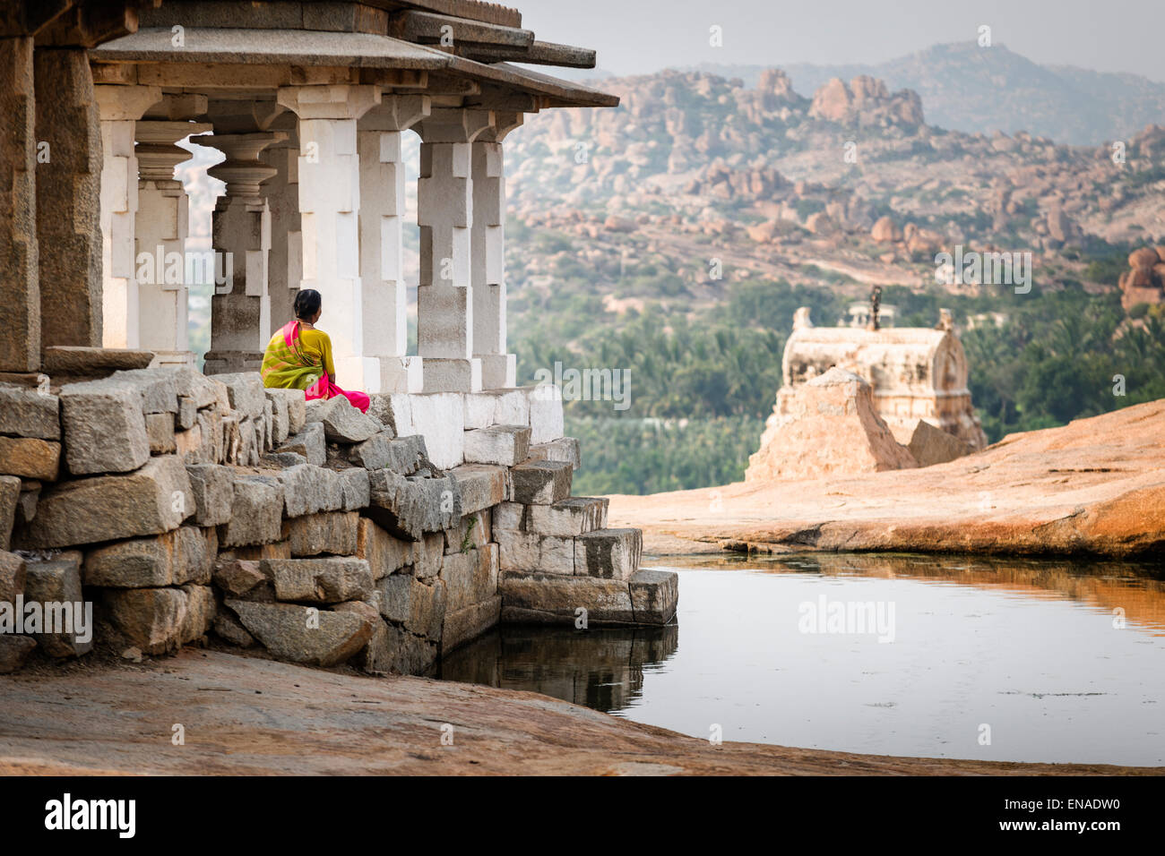 A woman sitting in some ancient ruins in Hampi. - Stock Image