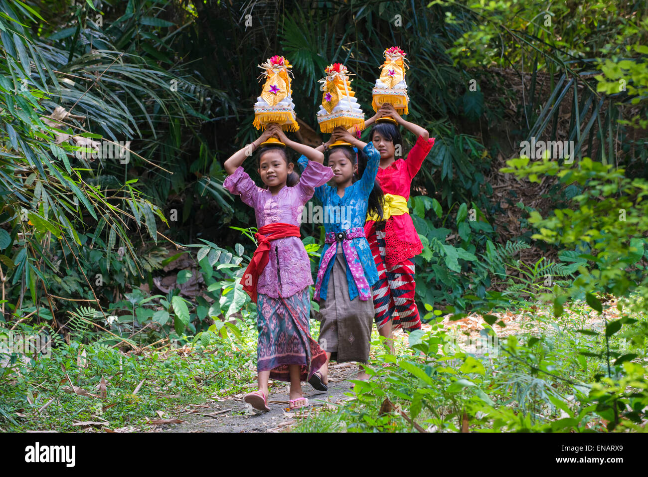 Three girls walking to the temple with offerings for a ceremony on the head, Bali, Indonesia - Stock Image
