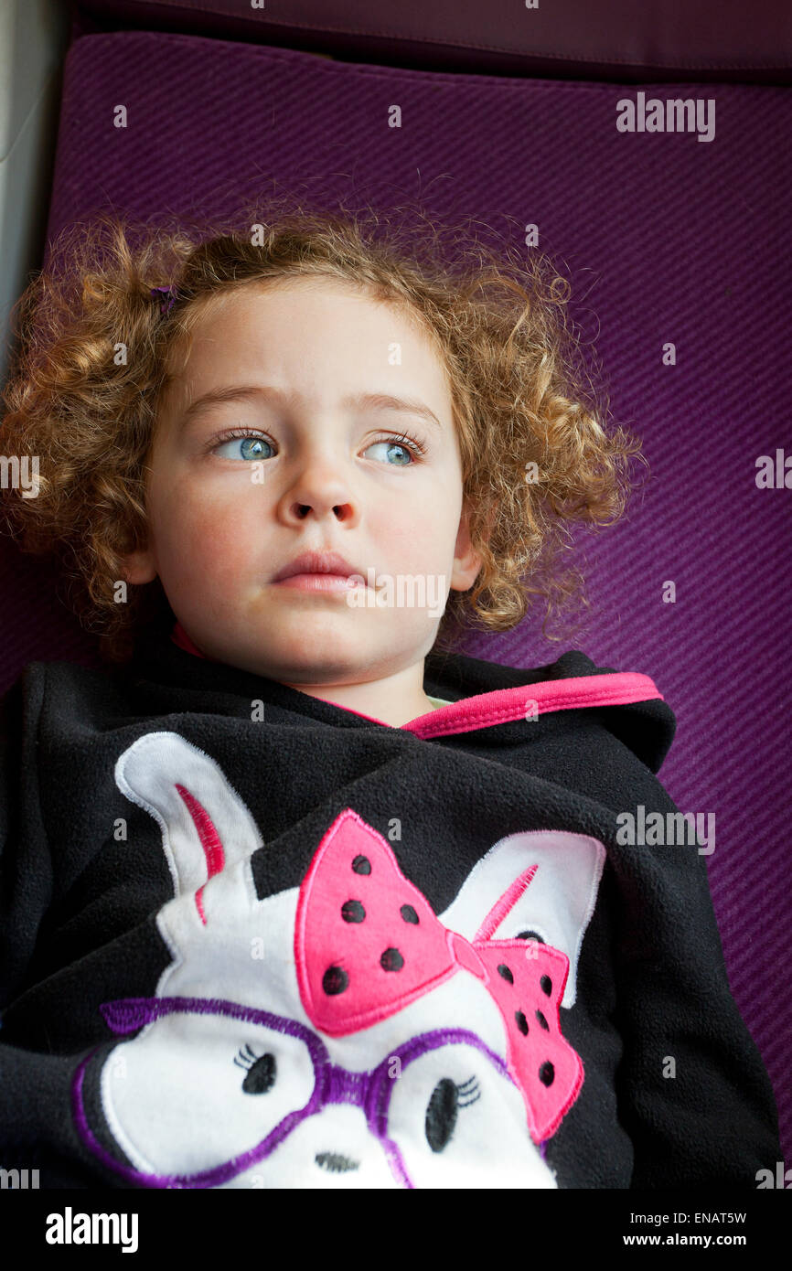 Curly haired three year old girl deep in thought - Stock Image