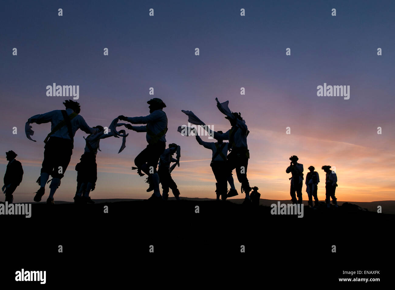 Morris dancers from the Chapel-en-le-Frith Morris Men dance at sunrise to welcome May Day on Eccles Pike - Stock Image