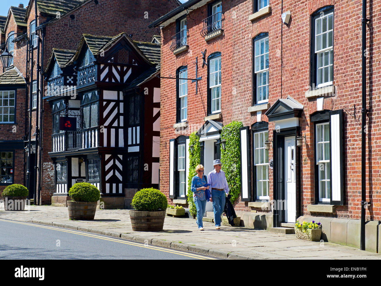 Middle aged couple walking down street in Prestbury, Cheshire, England UK - Stock Image
