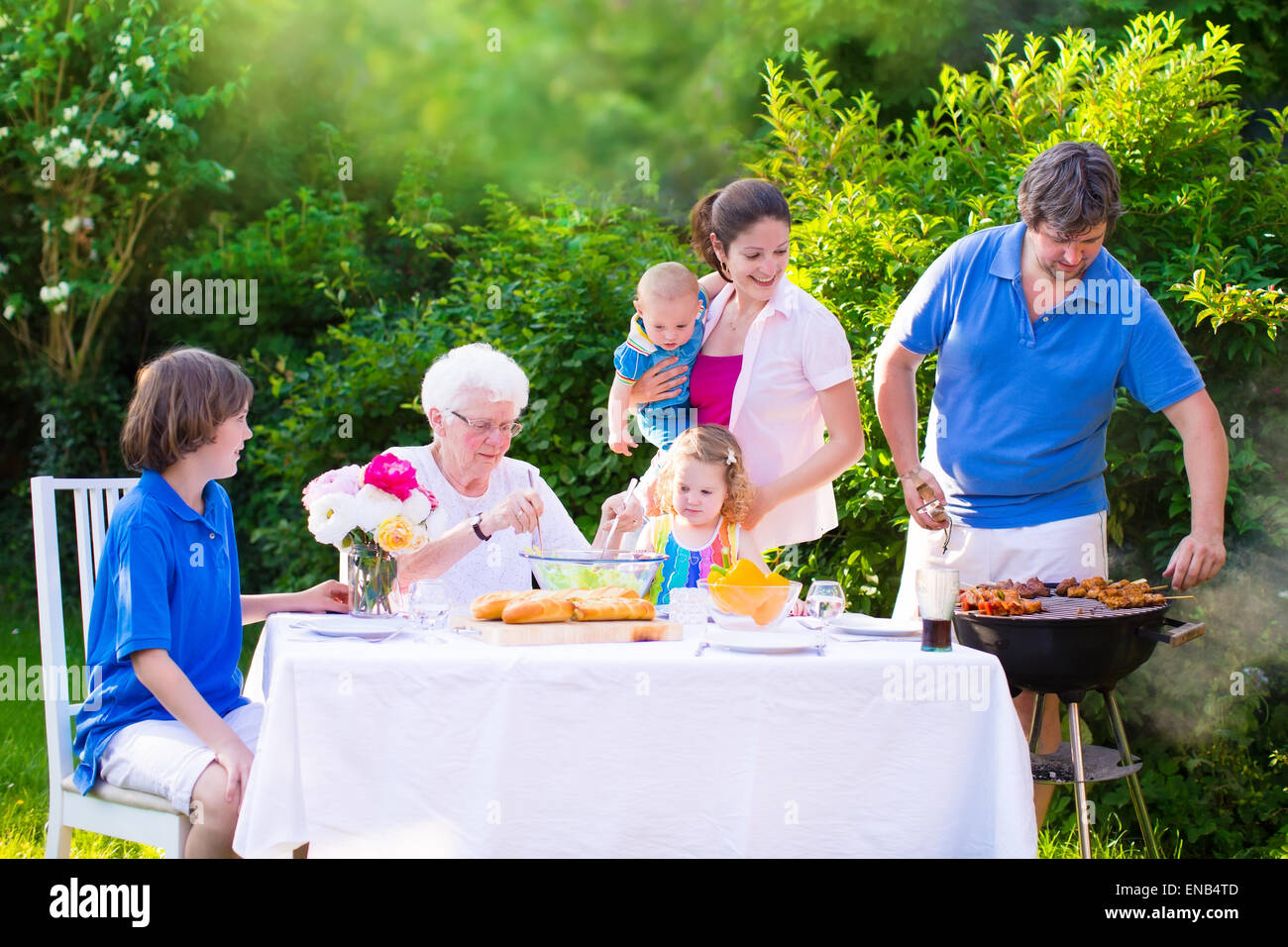 Grill barbecue backyard party. Happy big family enjoying BBQ lunch with grandmother - Stock Image