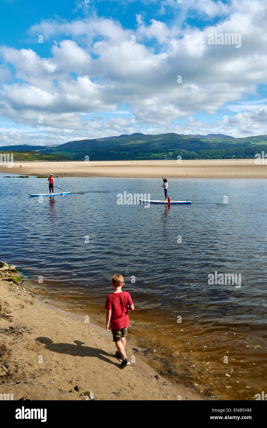 Children playing on the beach at Festival No.6, Portmeirion, Wales, UK and people wake boarding Stock Photo