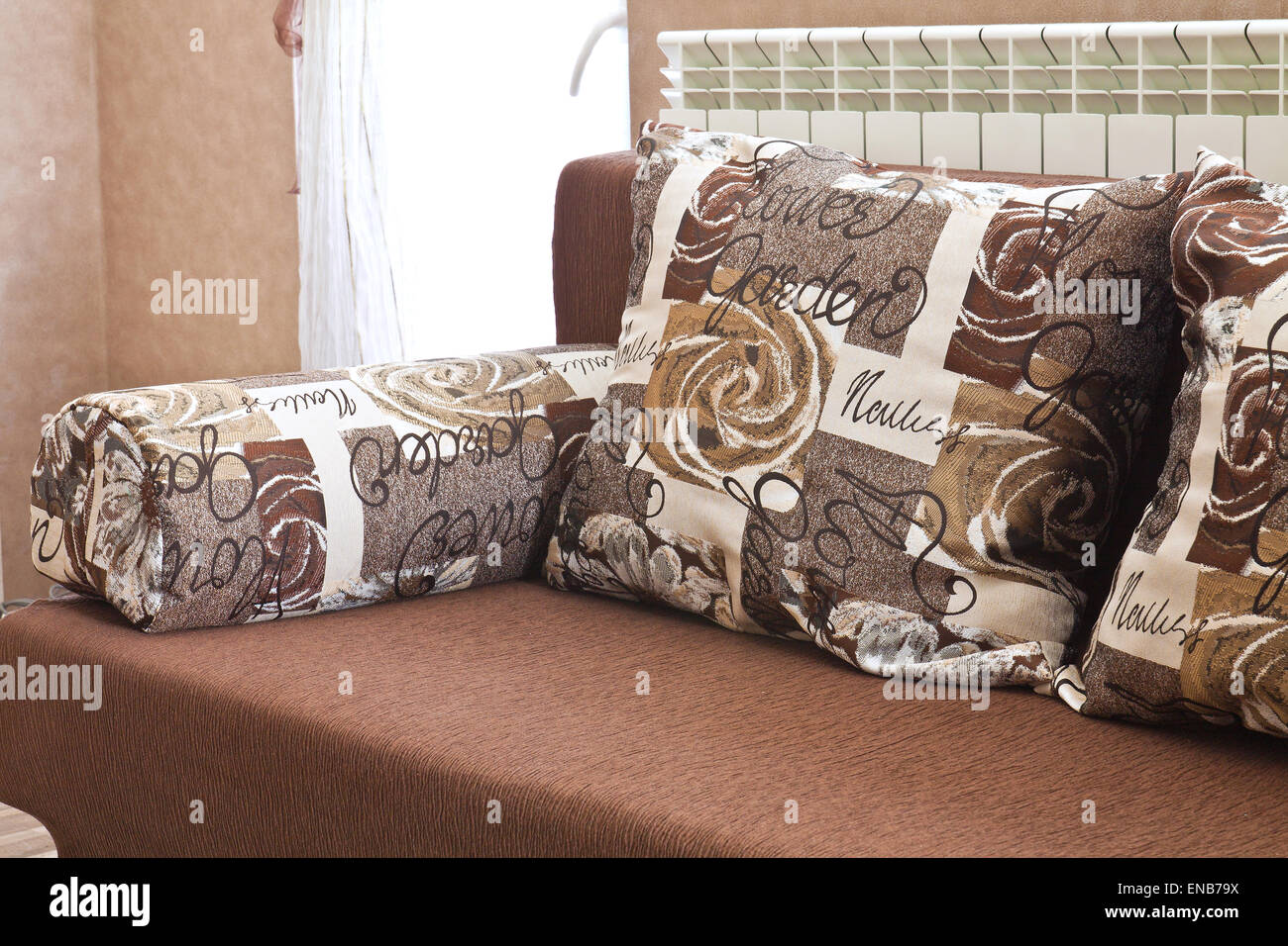 Detail from home sofa with pillows in beige brown tones - Stock Image