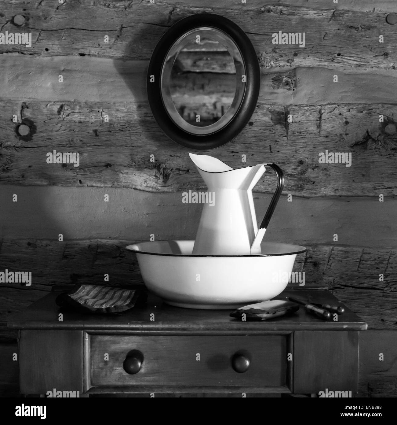 Antique wash bowl and pitcher displayed on dresser in log cabin at Log Cabin Village, Fort Worth, Texas - Stock Image