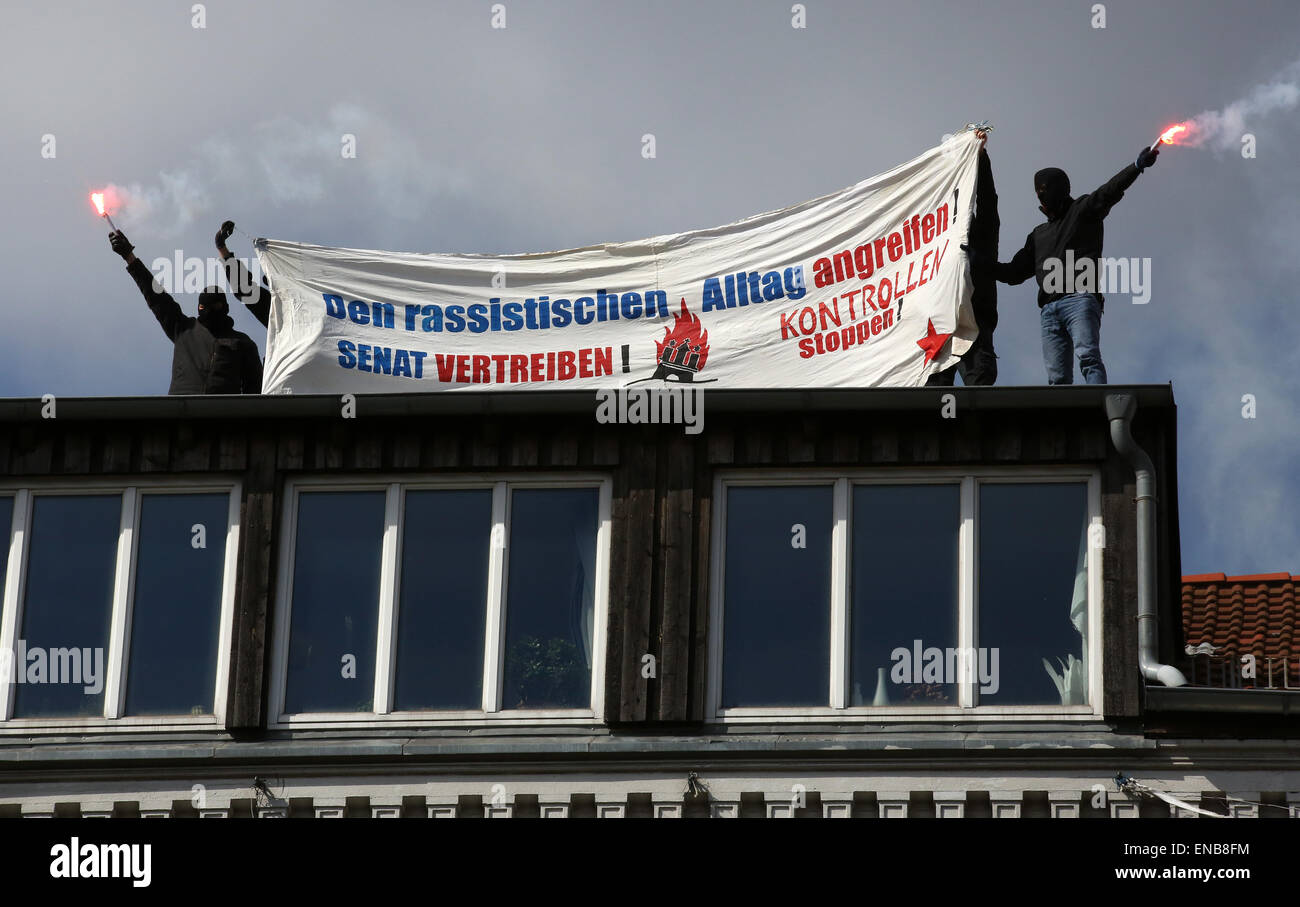 Hamburg, Germany. 01st May, 2015. Masked people with flares on the roof of a formerly occupied house hold up a banner - Stock Image