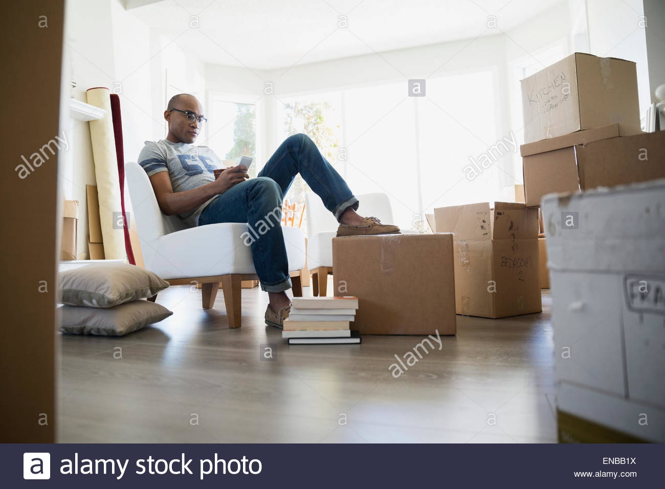 Man texting surrounded by moving boxes - Stock Image