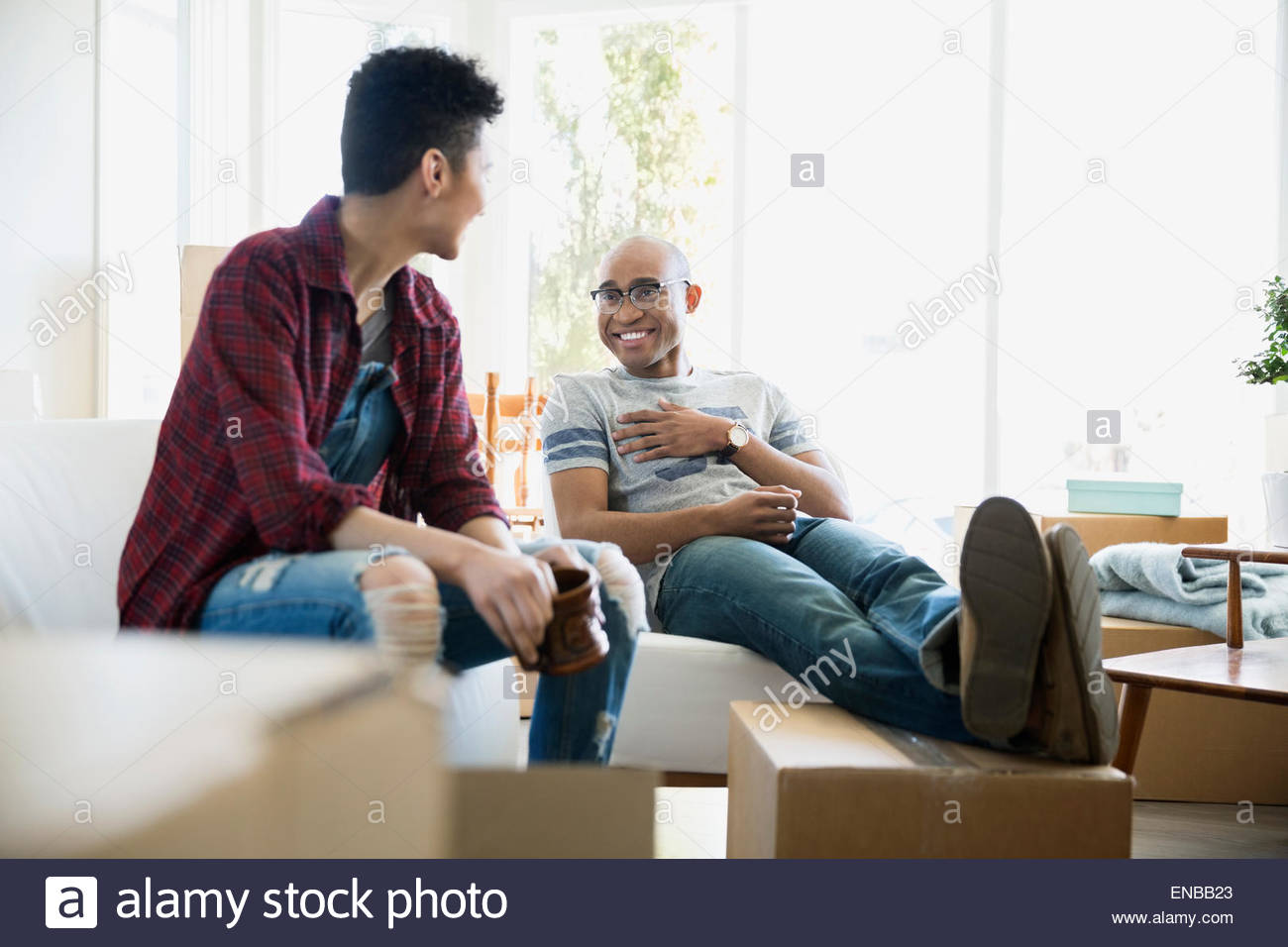 Couple relaxing surrounded by moving boxes - Stock Image