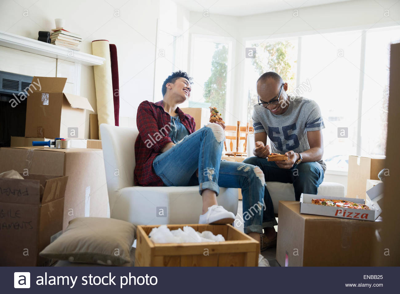 Couple surrounded by moving boxes enjoying takeout pizza - Stock Image