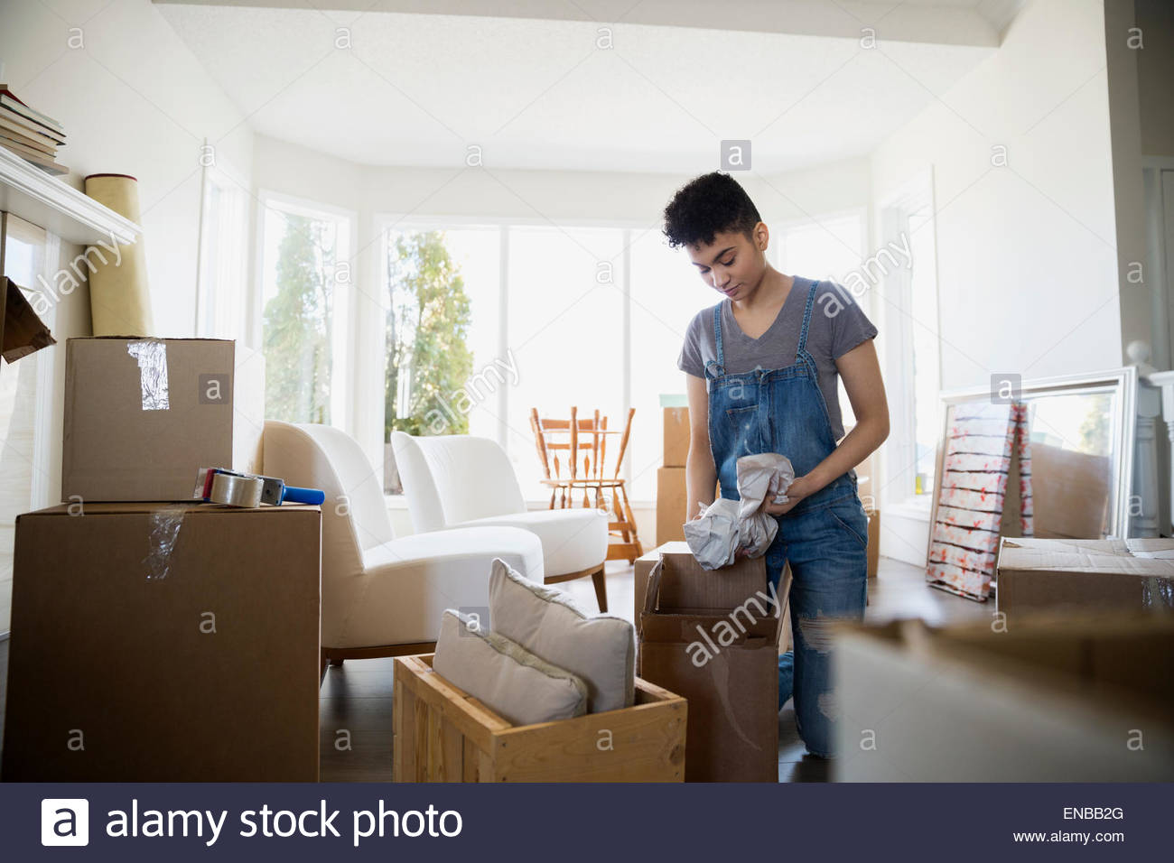 Woman packing belongings in moving boxes - Stock Image