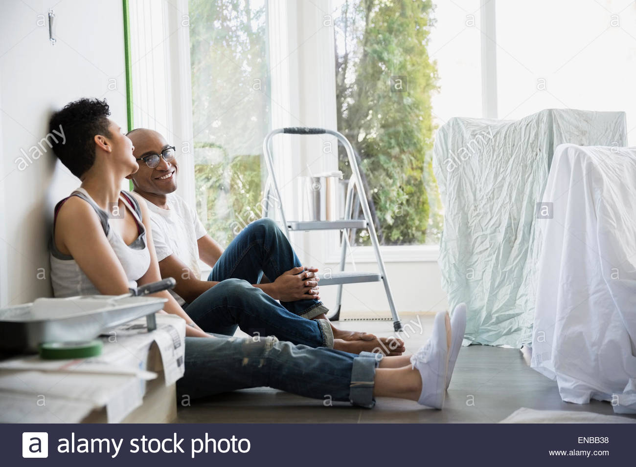 Couple taking a break from painting living room - Stock Image