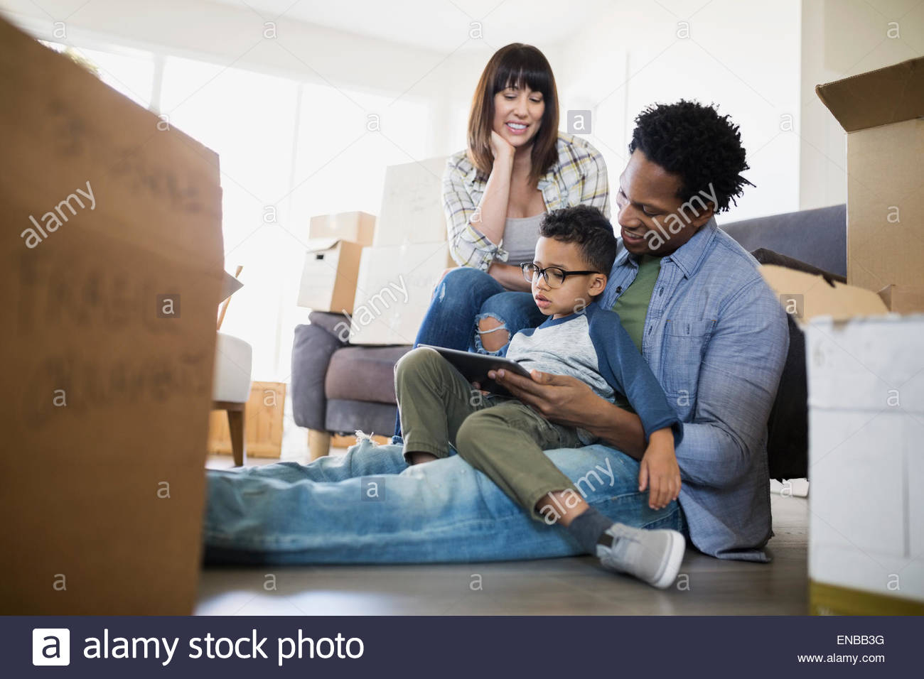 Moving boxes surrounding family using digital tablet - Stock Image