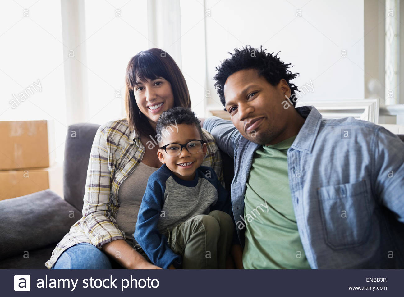 Portrait of smiling family moving in - Stock Image