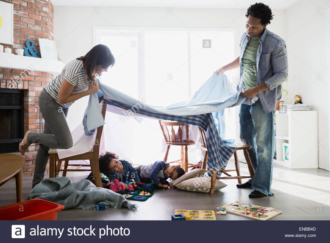 Parents creating fort over sleeping children - Stock Image