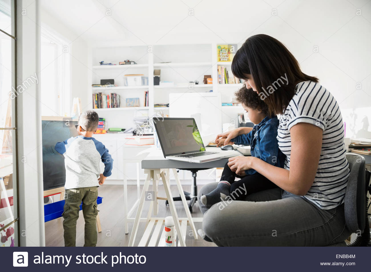 Mother and daughter at laptop in home office - Stock Image