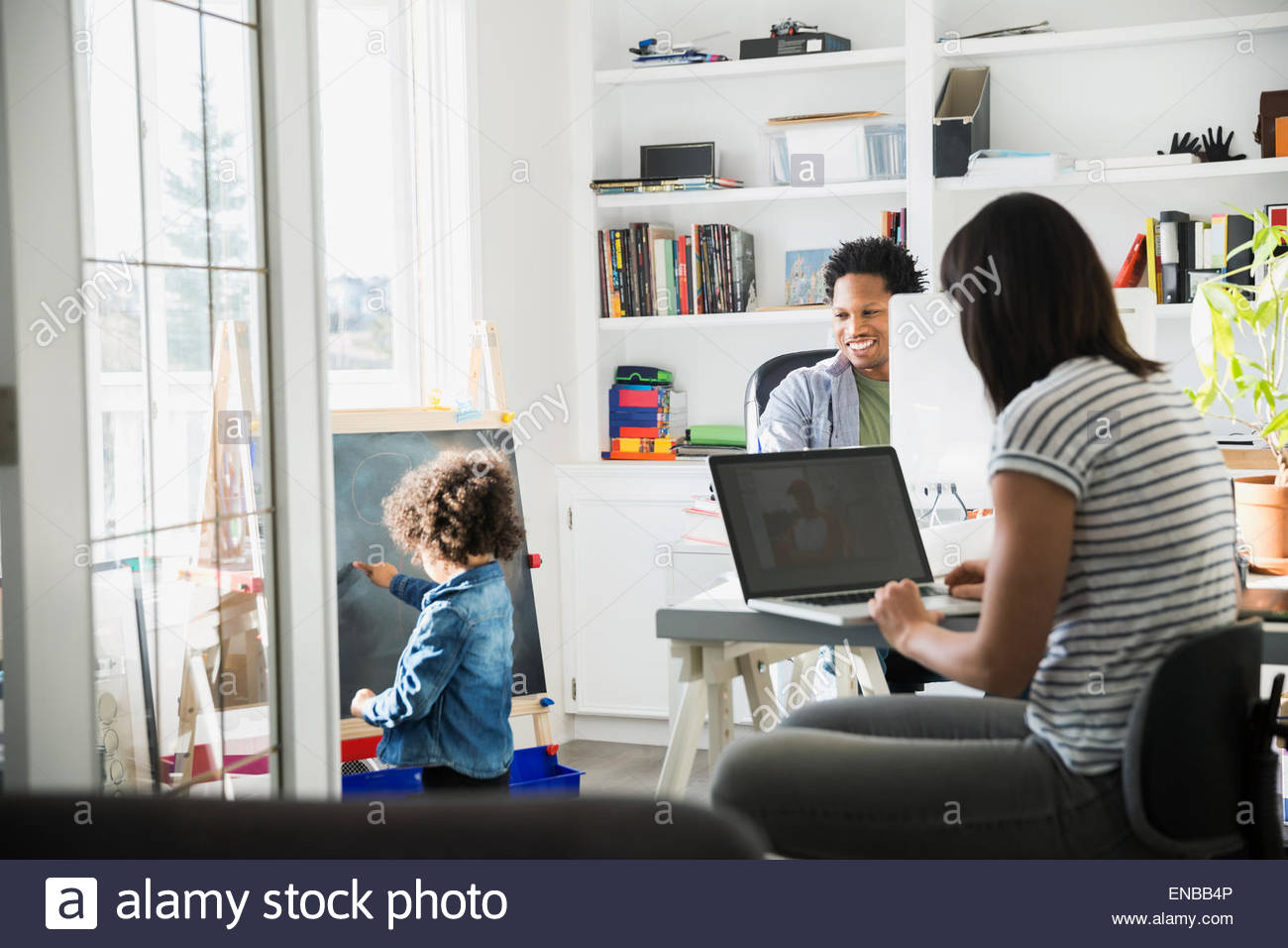 Parents working at computers with daughter playing nearby - Stock Image