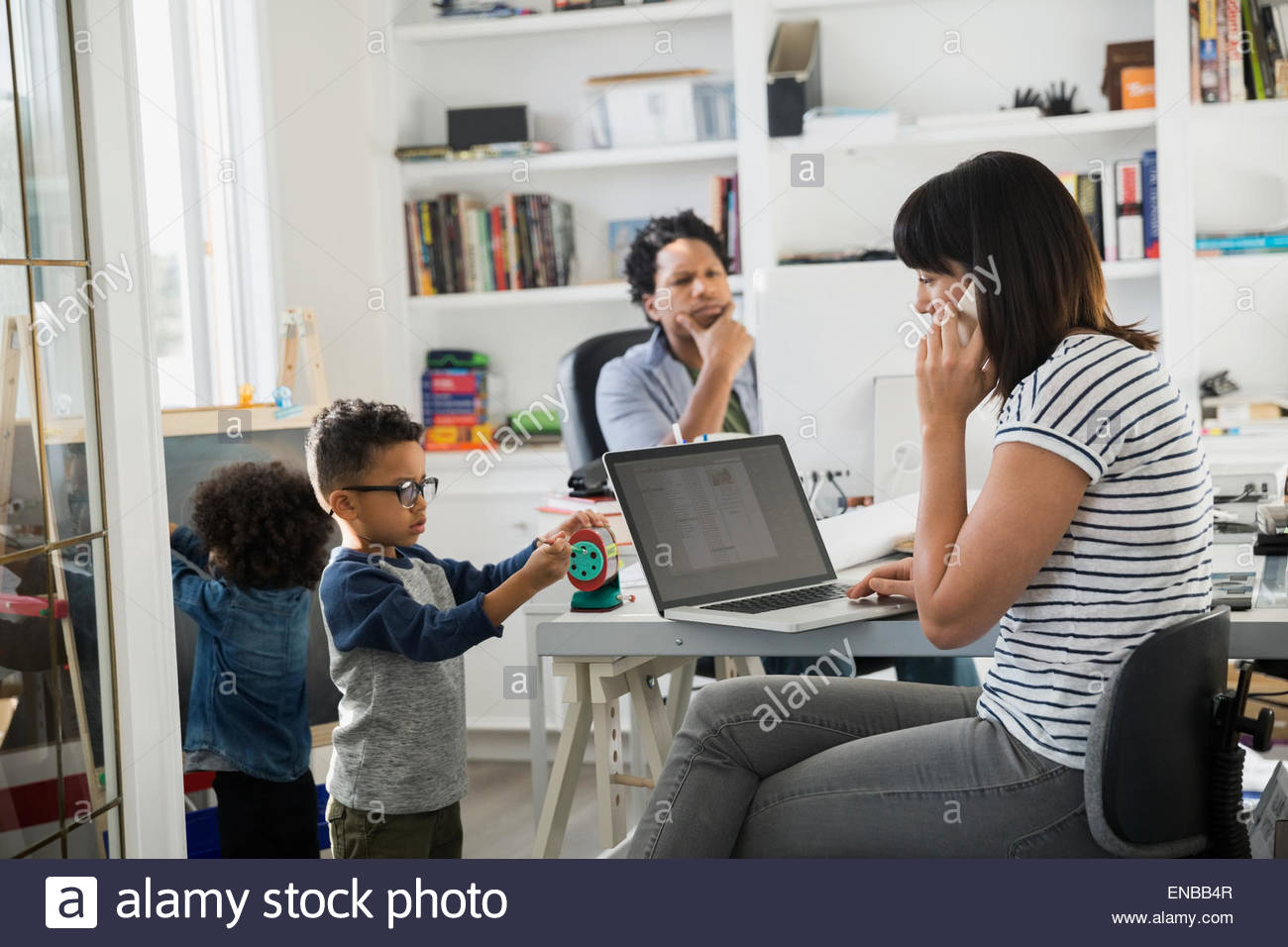 Parents working in home office with children playing - Stock Image