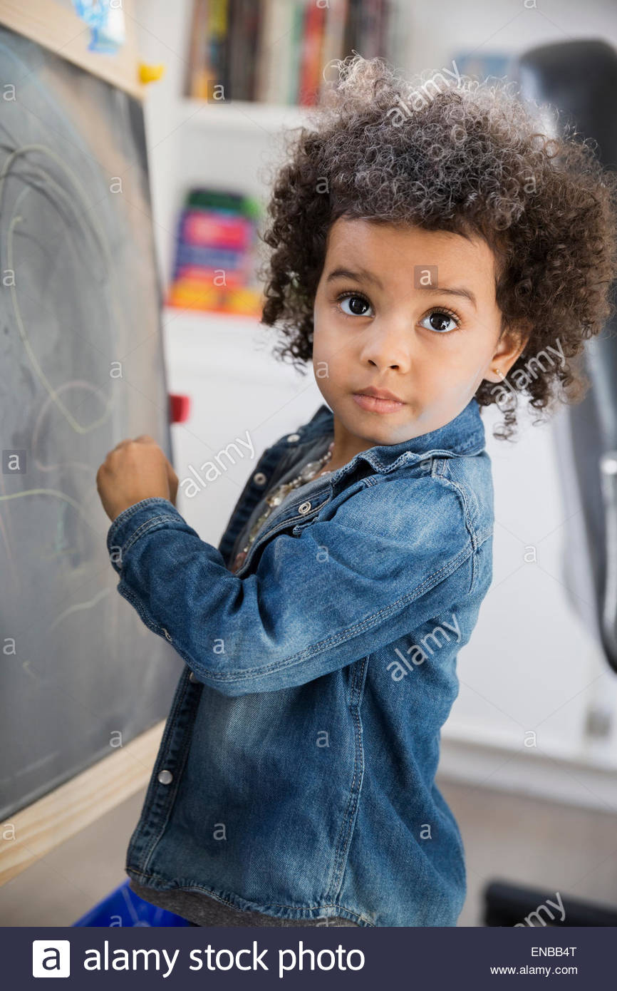 Girl with curly hair drawing at blackboard Stock Photo