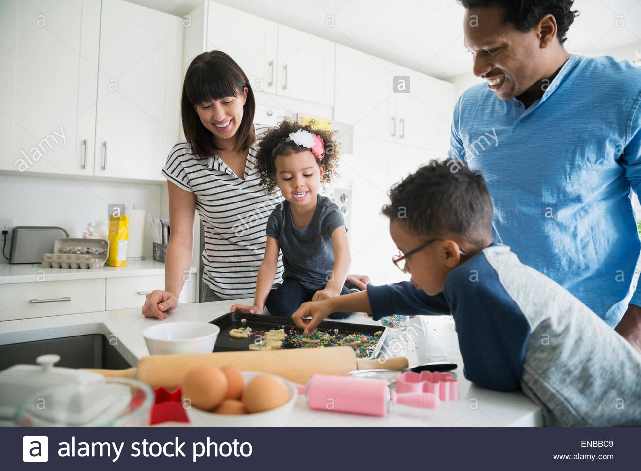 Family baking and decorating sugar cookies in kitchen - Stock Image