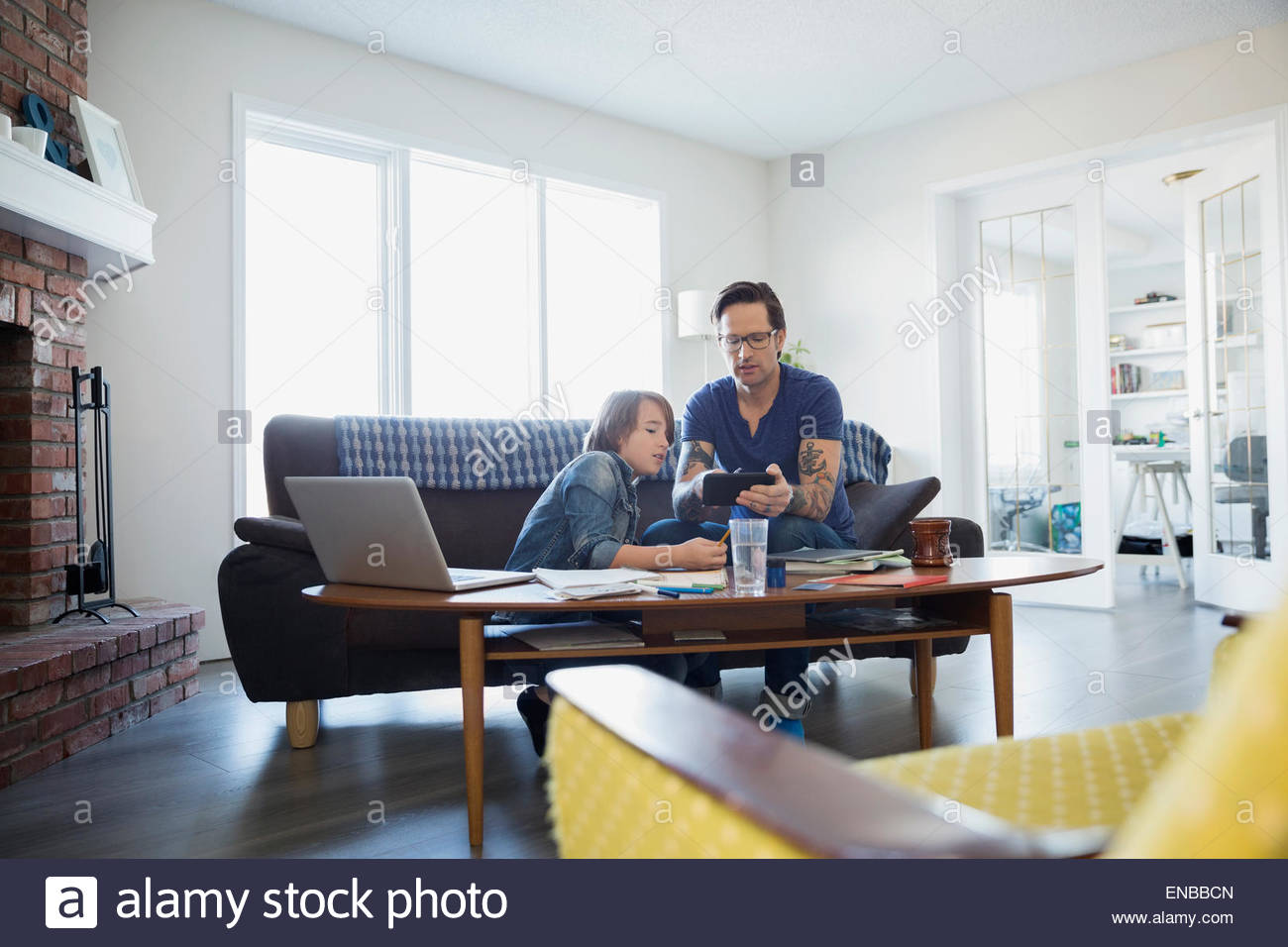 Father helping son with homework in living room - Stock Image