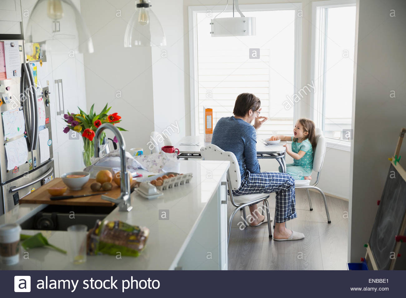 Father and daughter in pajamas enjoying breakfast - Stock Image