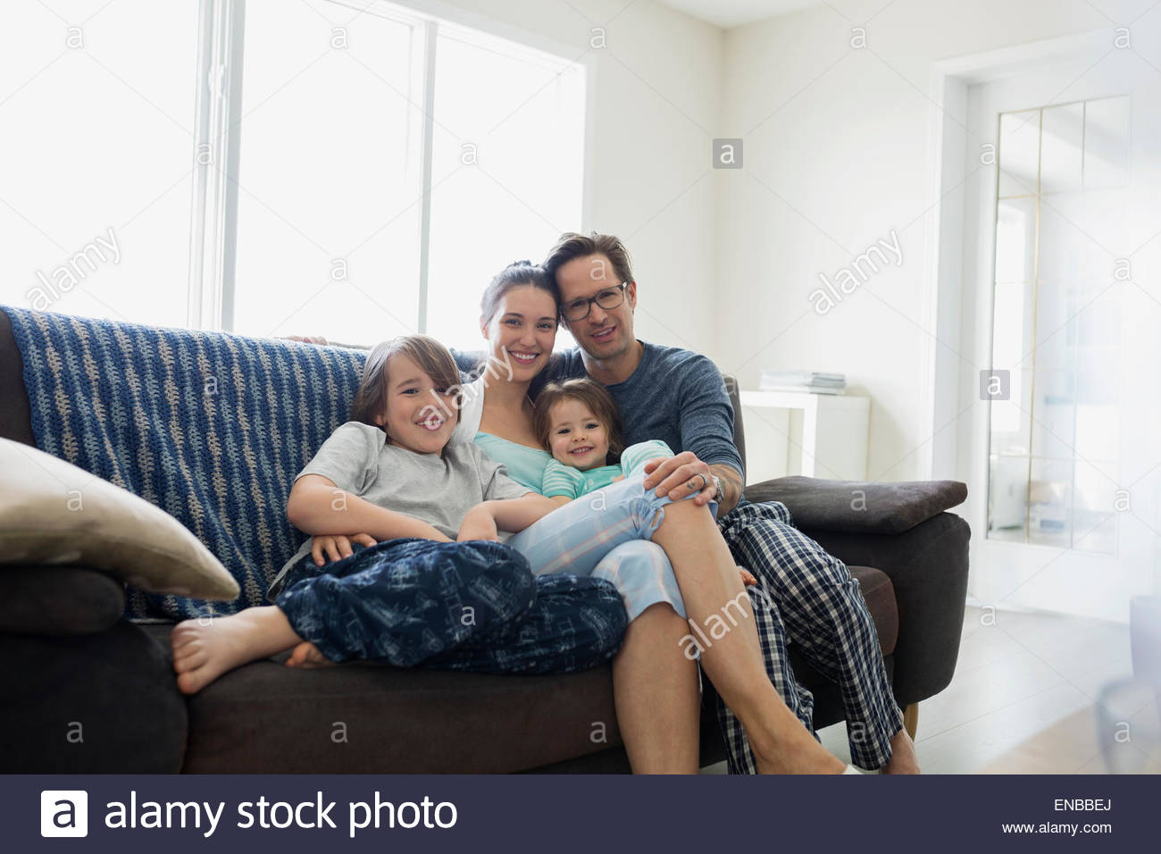 Portrait of smiling family in pajamas relaxing sofa - Stock Image