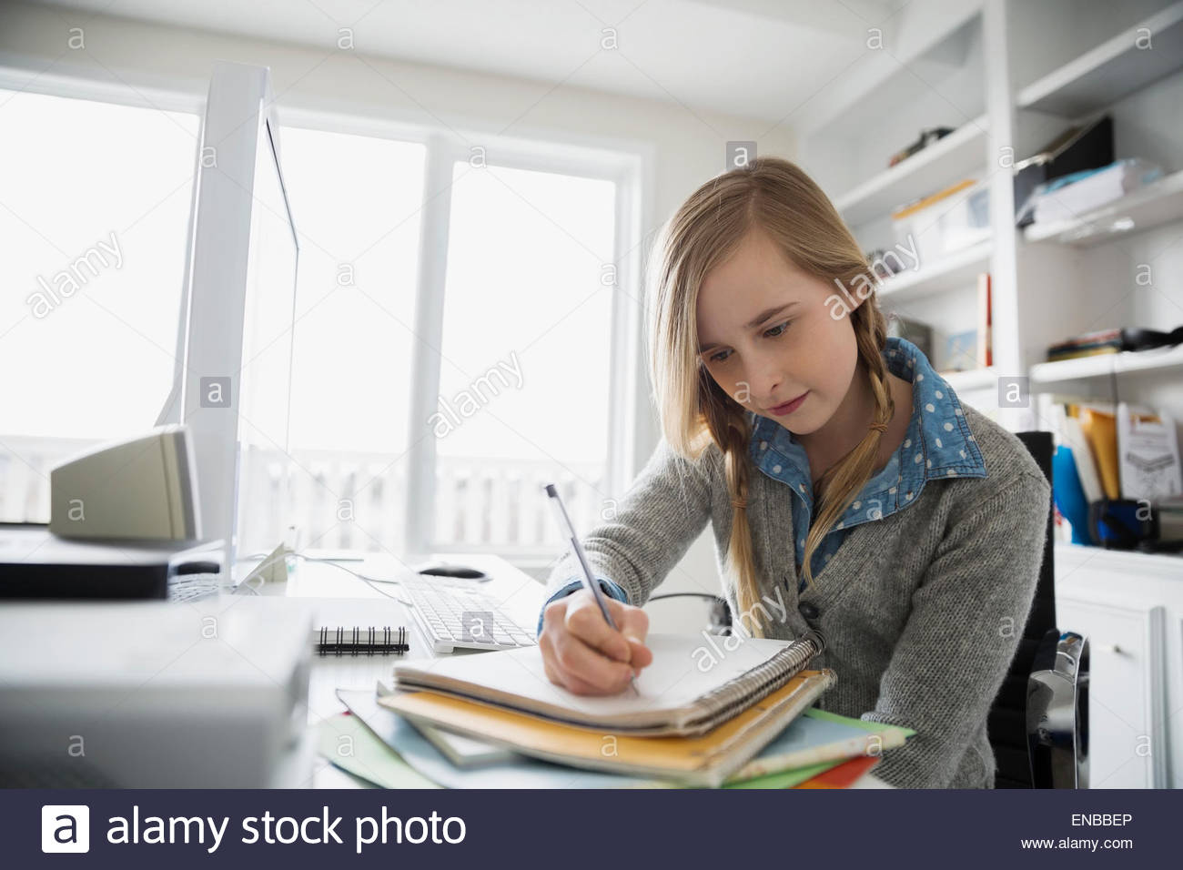 Girl doing homework in home office - Stock Image
