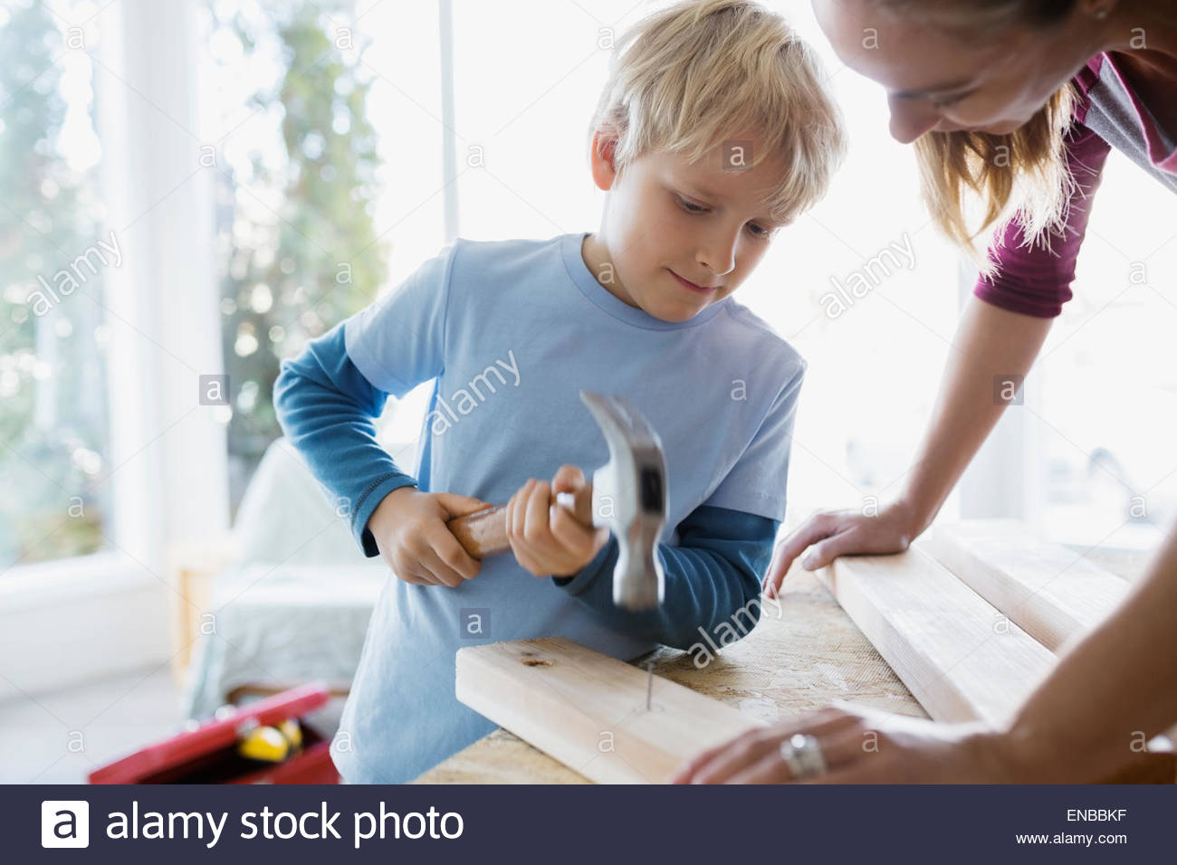 Mother helping son hammer nail into wood trim - Stock Image