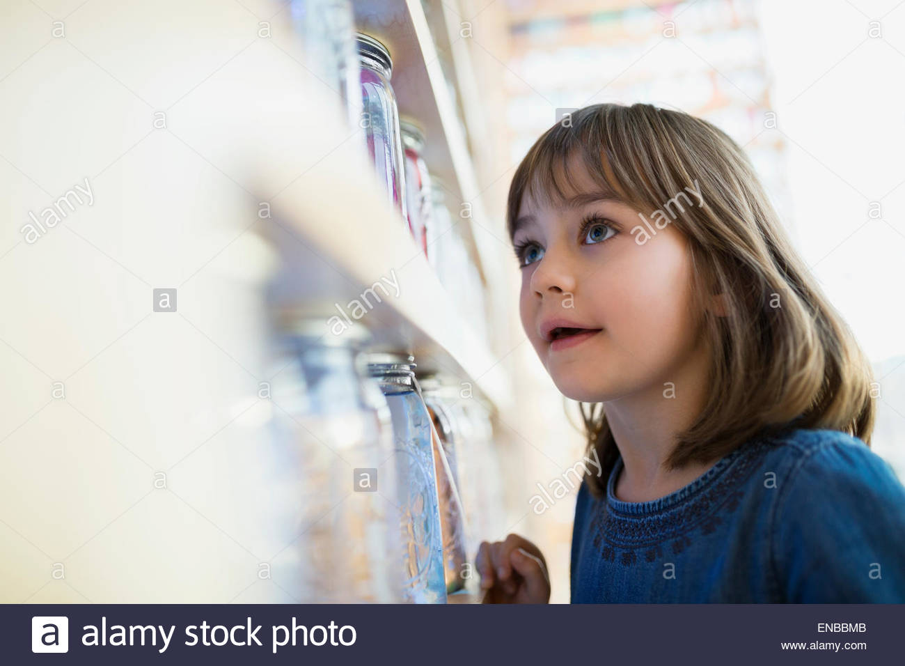 Curious girl examining jars in science center - Stock Image
