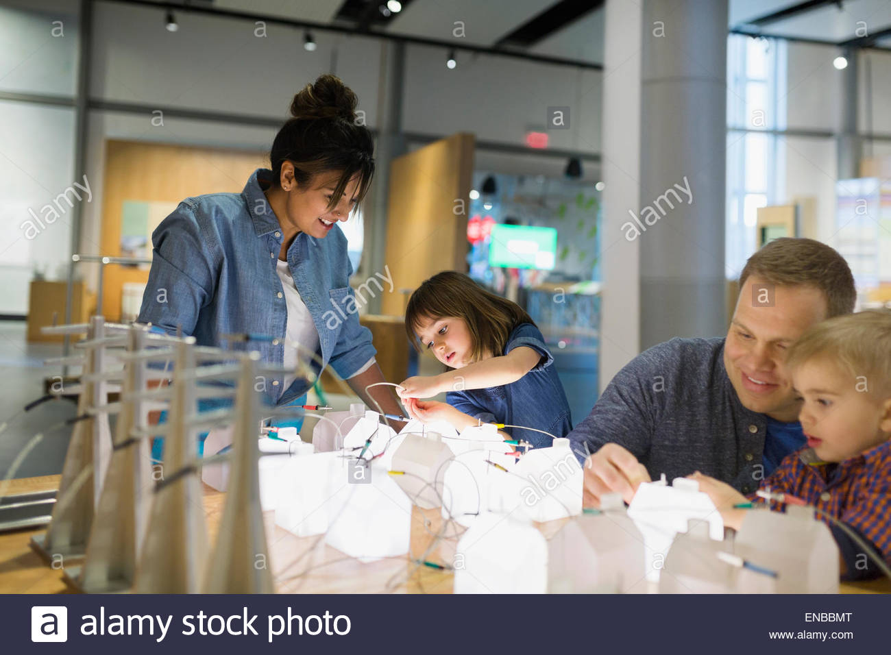 Family playing with electricity grid at science center - Stock Image