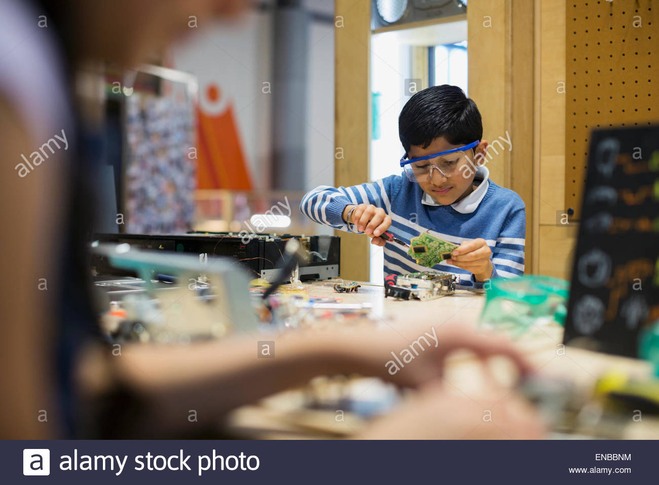 Boy wearing goggles assembling electronics at science center - Stock Image