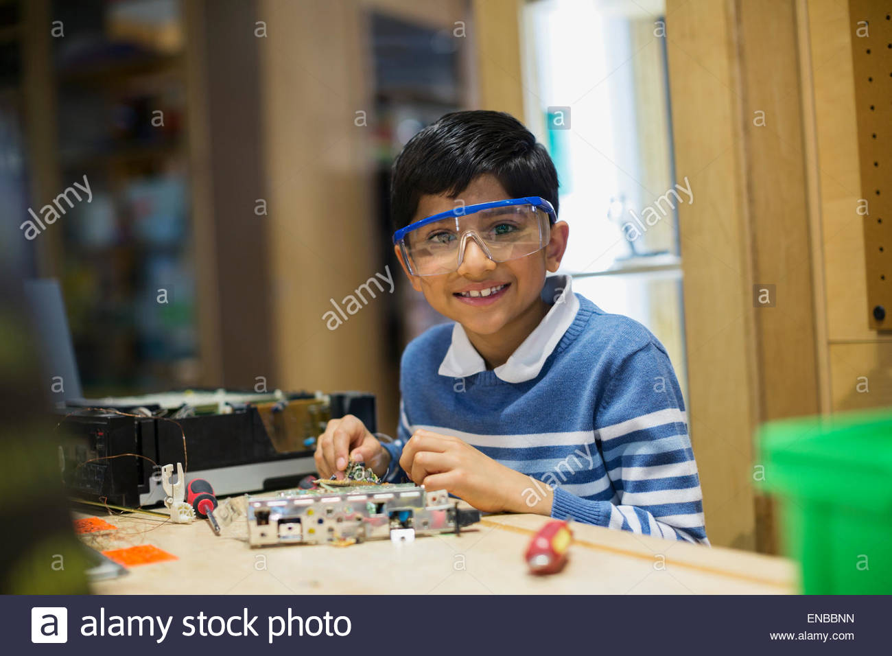 Portrait of smiling boy assembling electronics science center - Stock Image