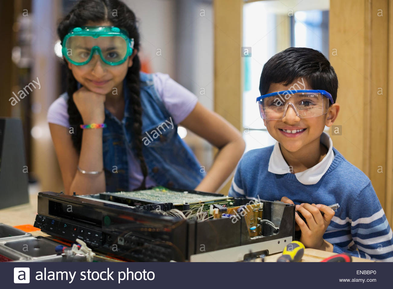 Portrait of confident brother and sister assembling electronics - Stock Image