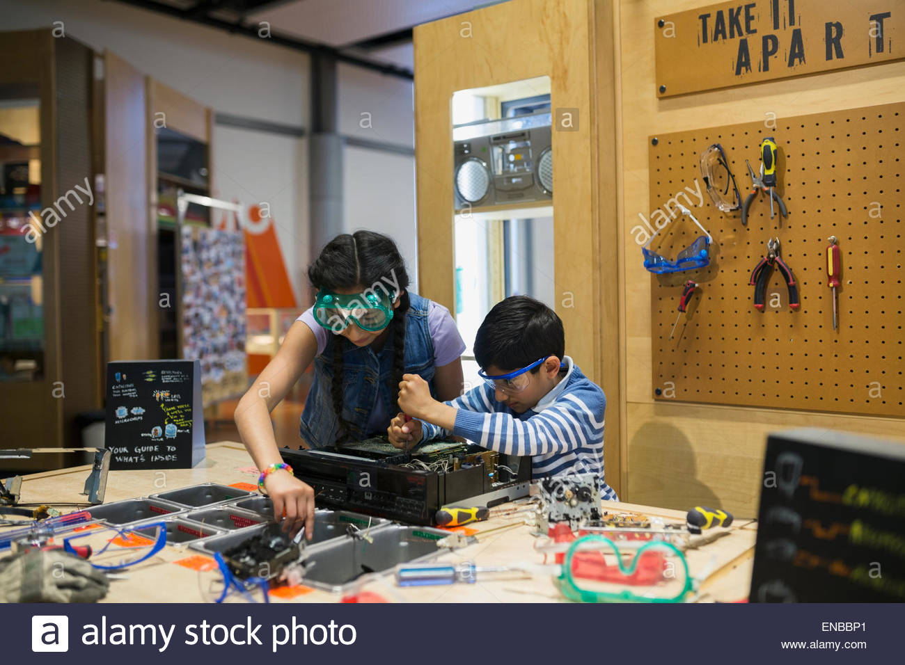 Brother and sister assembling electronics at science center - Stock Image