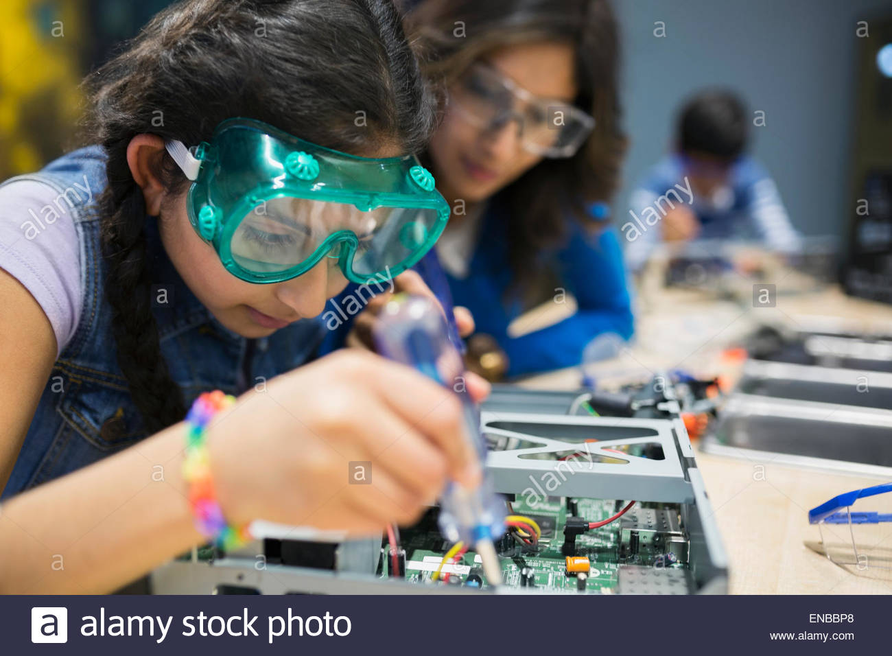 Mother watching daughter assembling electronics at science center - Stock Image