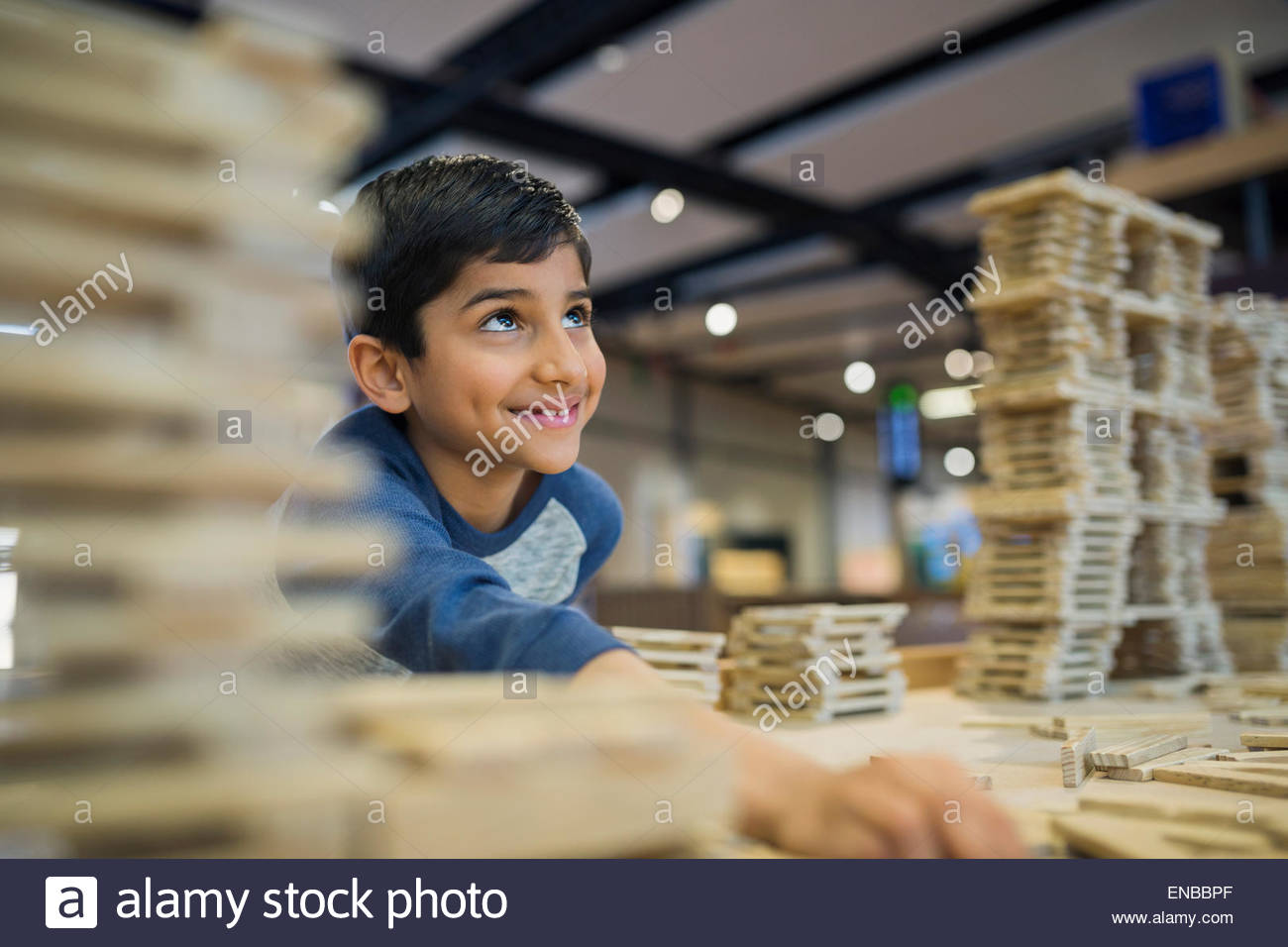 Boy assembling wood block structure at science center - Stock Image
