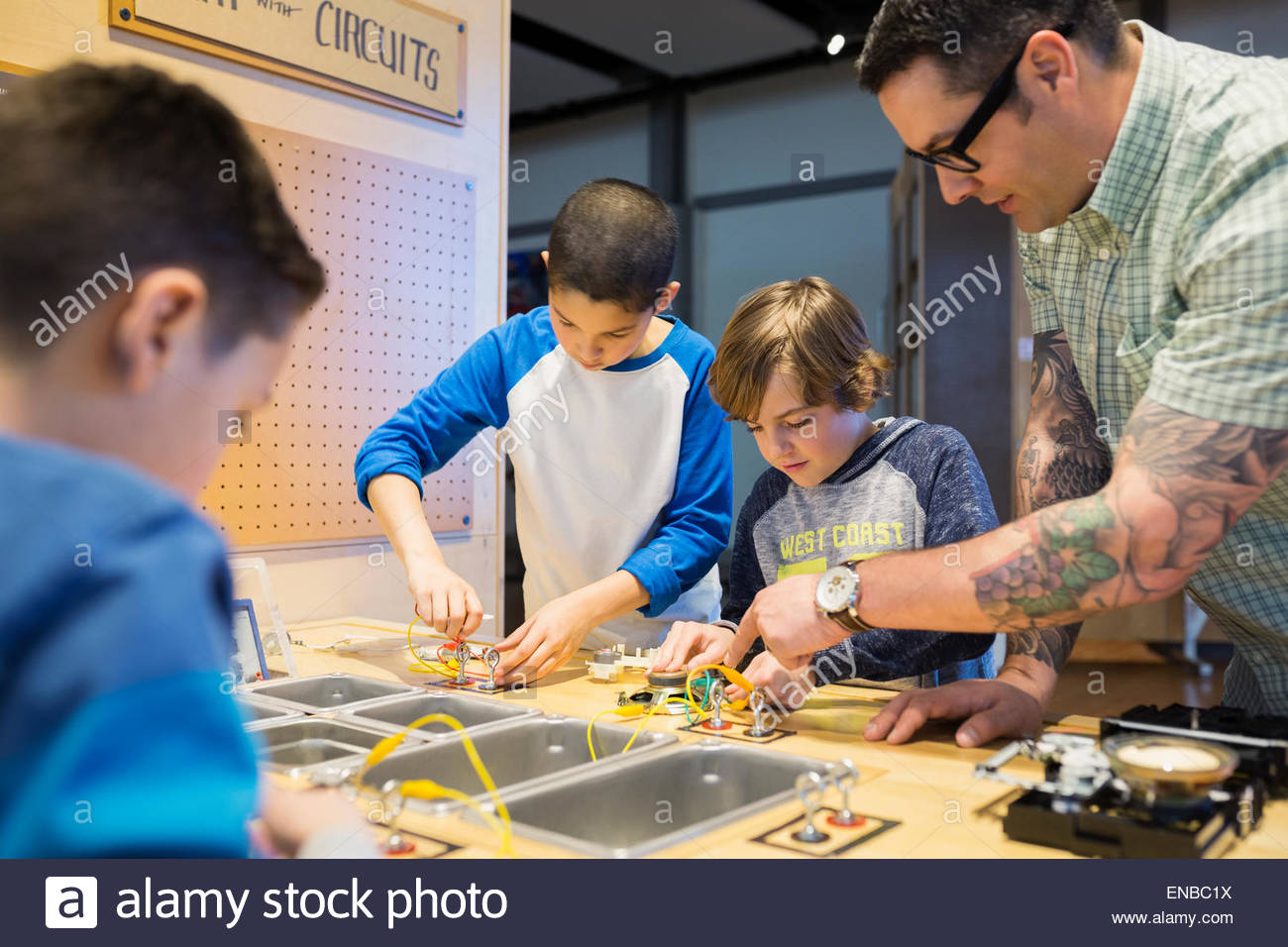 Teacher and students assembling electronic circuits science center - Stock Image
