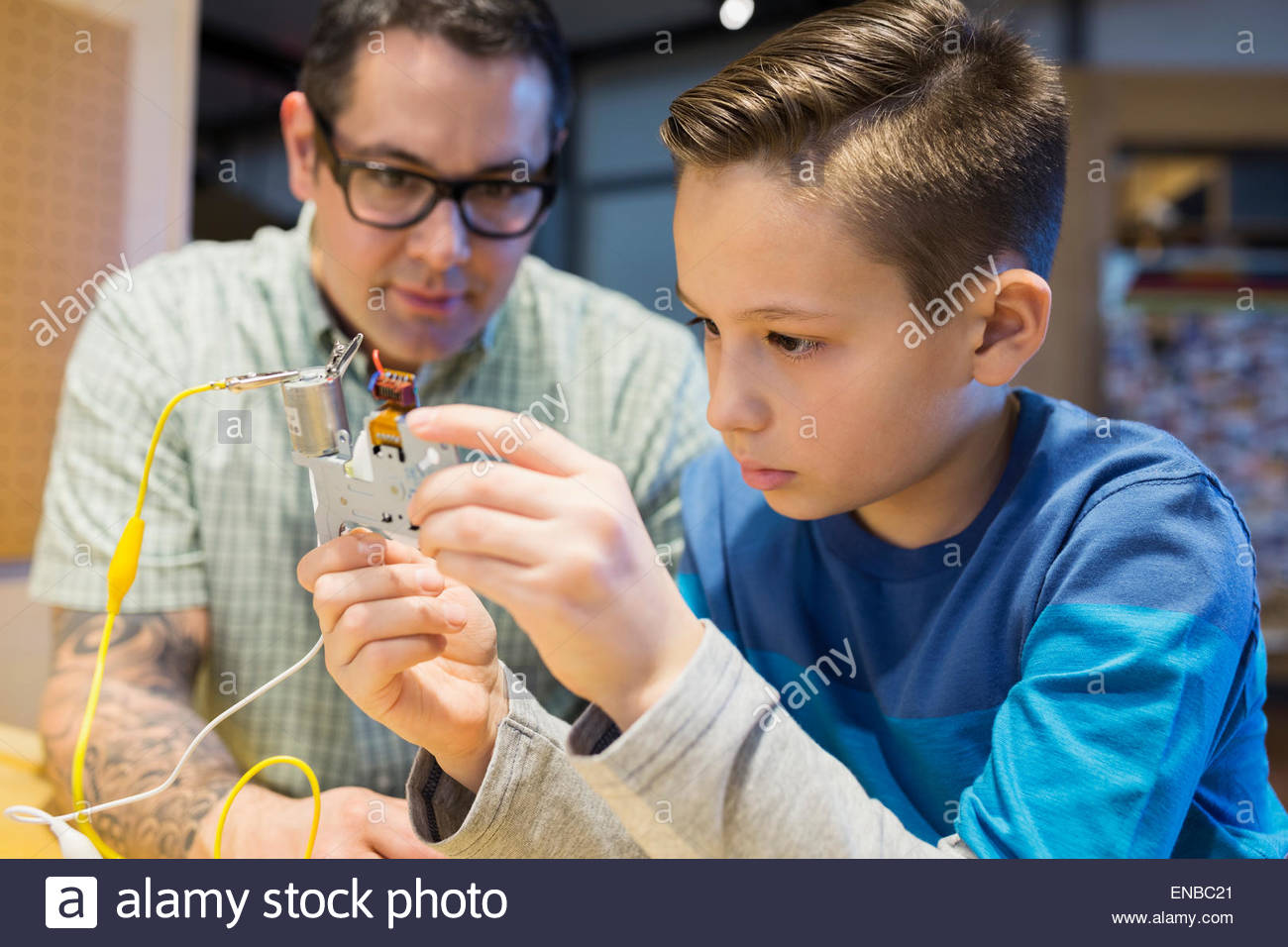 Teacher and student assembling electronic circuit science center Stock Photo