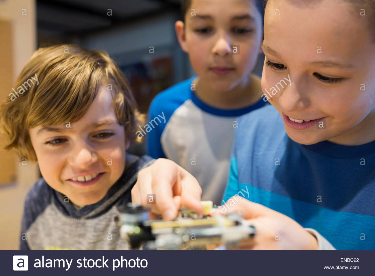 Close up boys assembling electronic circuit science center - Stock Image