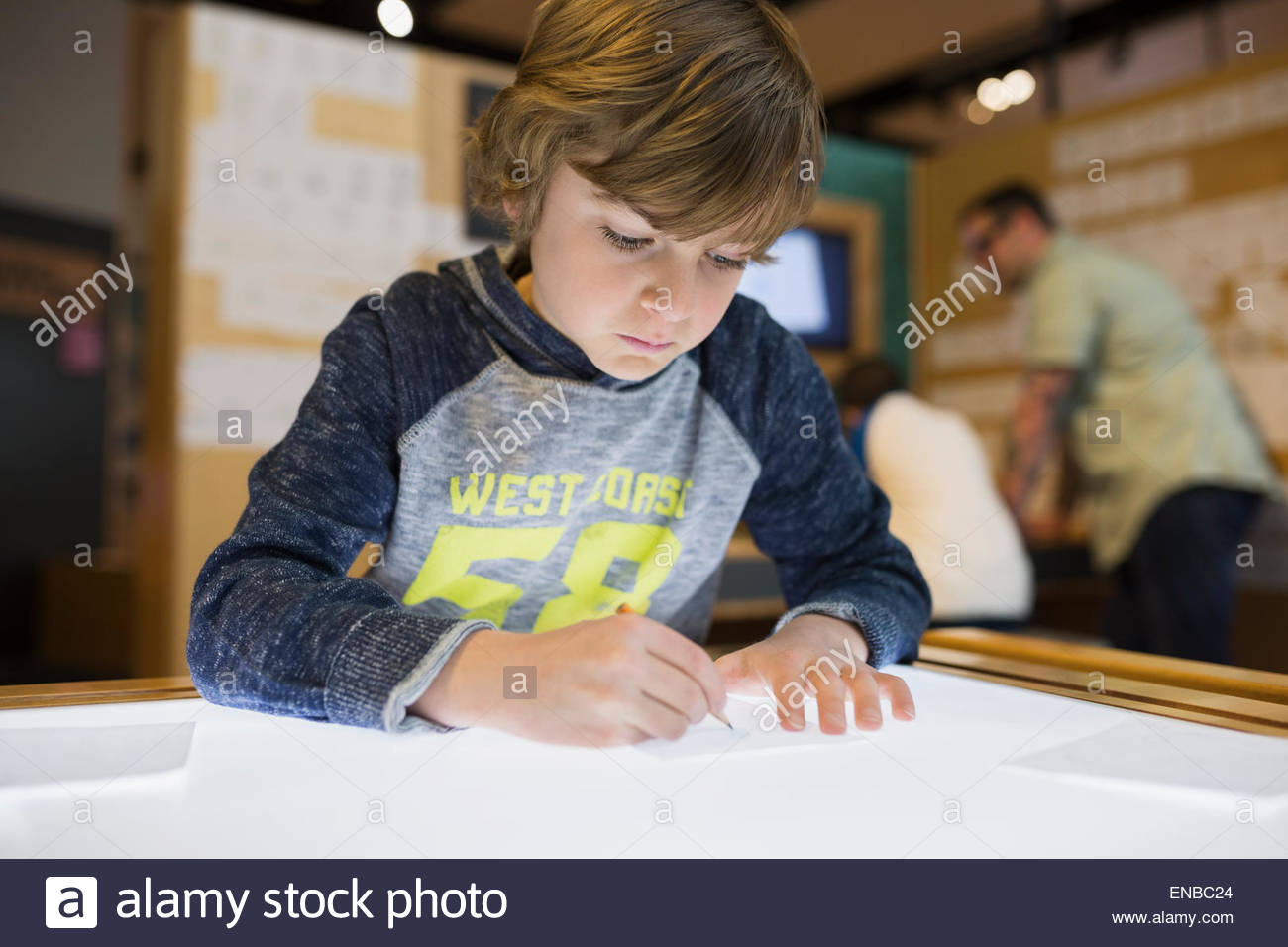 Boy tracing on light table at science center - Stock Image