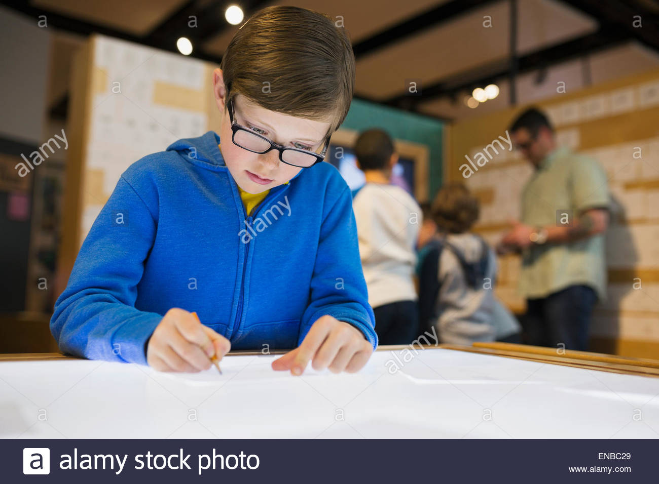 Boy tracing at light table at science center - Stock Image