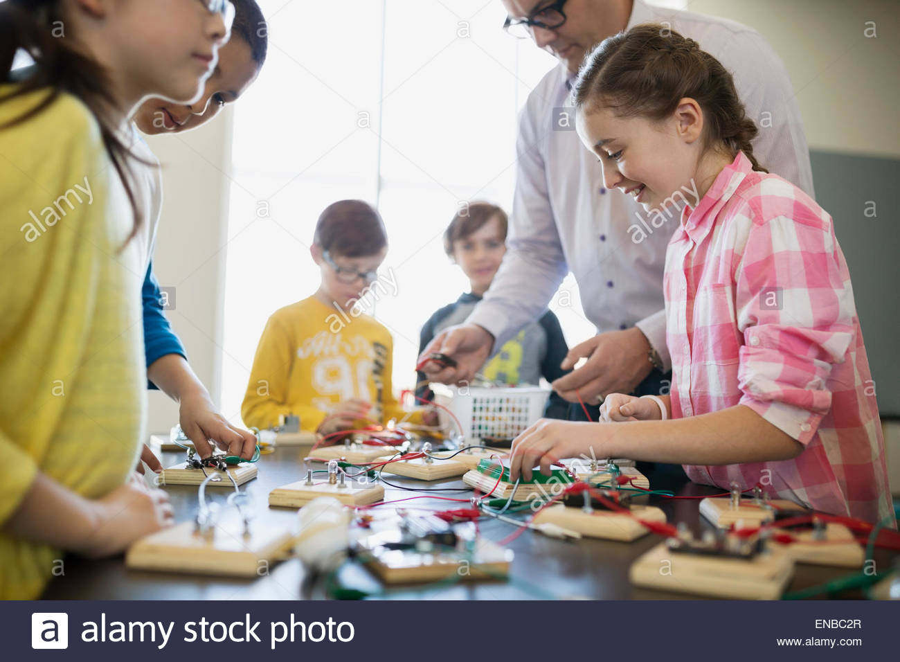 Students and teacher assembling circuit electronics at table - Stock Image