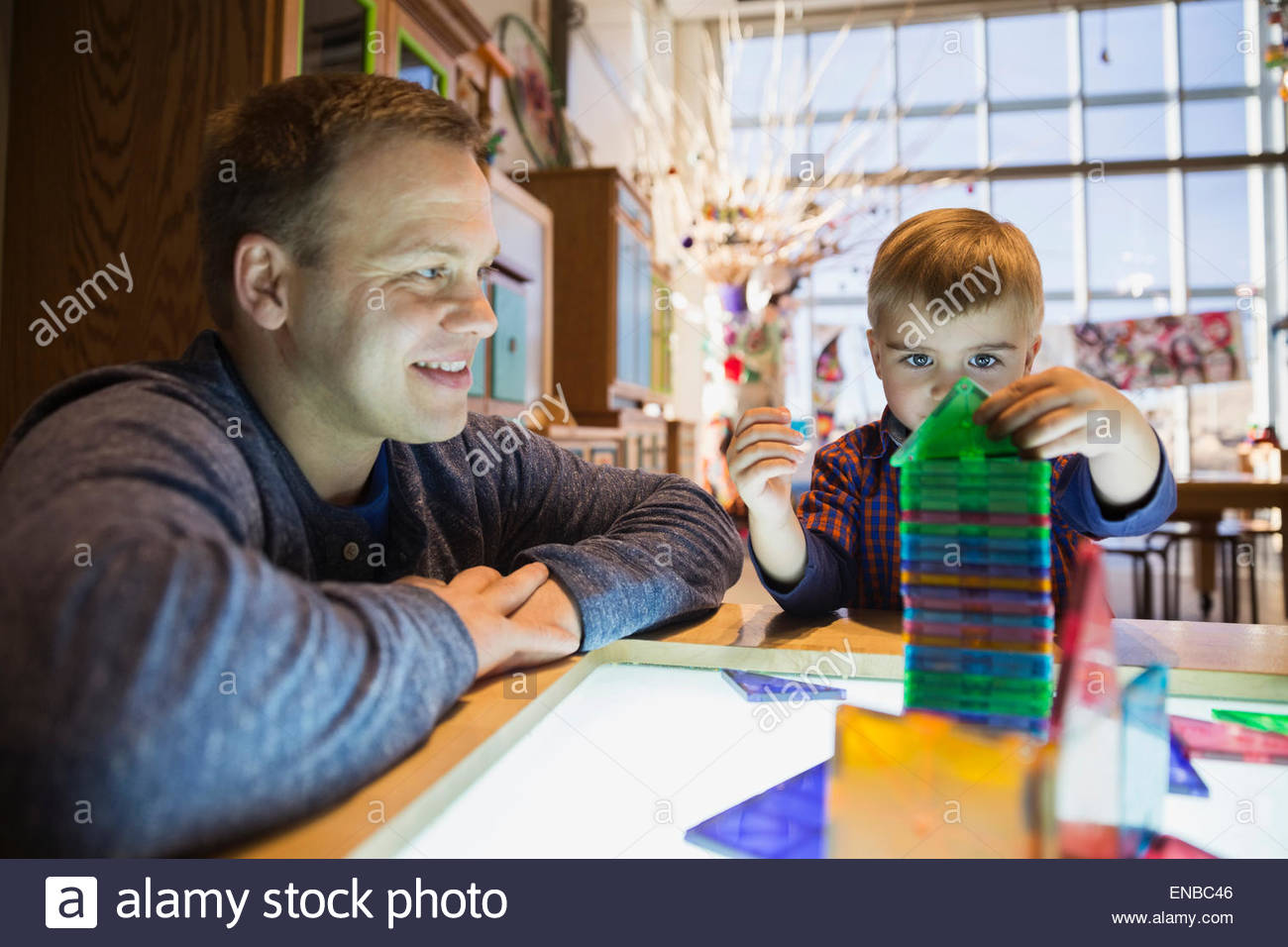 Father watching son stack model pieces science center - Stock Image