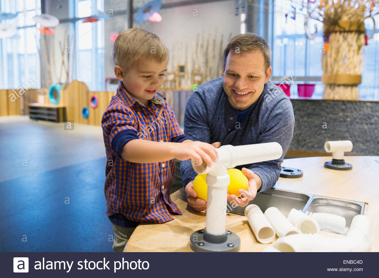Father and son assembling pipeline at science center - Stock Image
