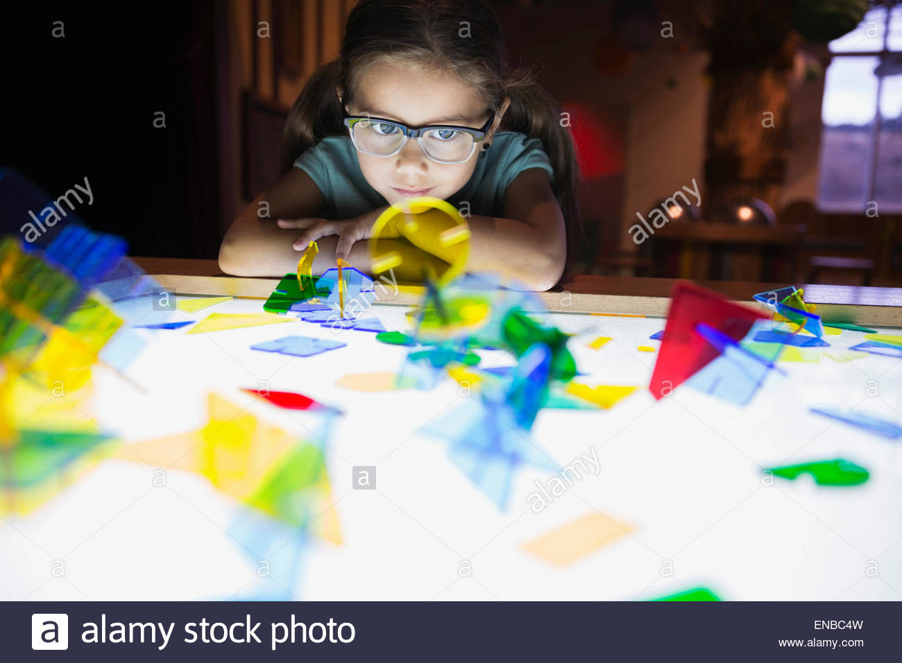Curious girl watching geometric shapes at science center - Stock Image