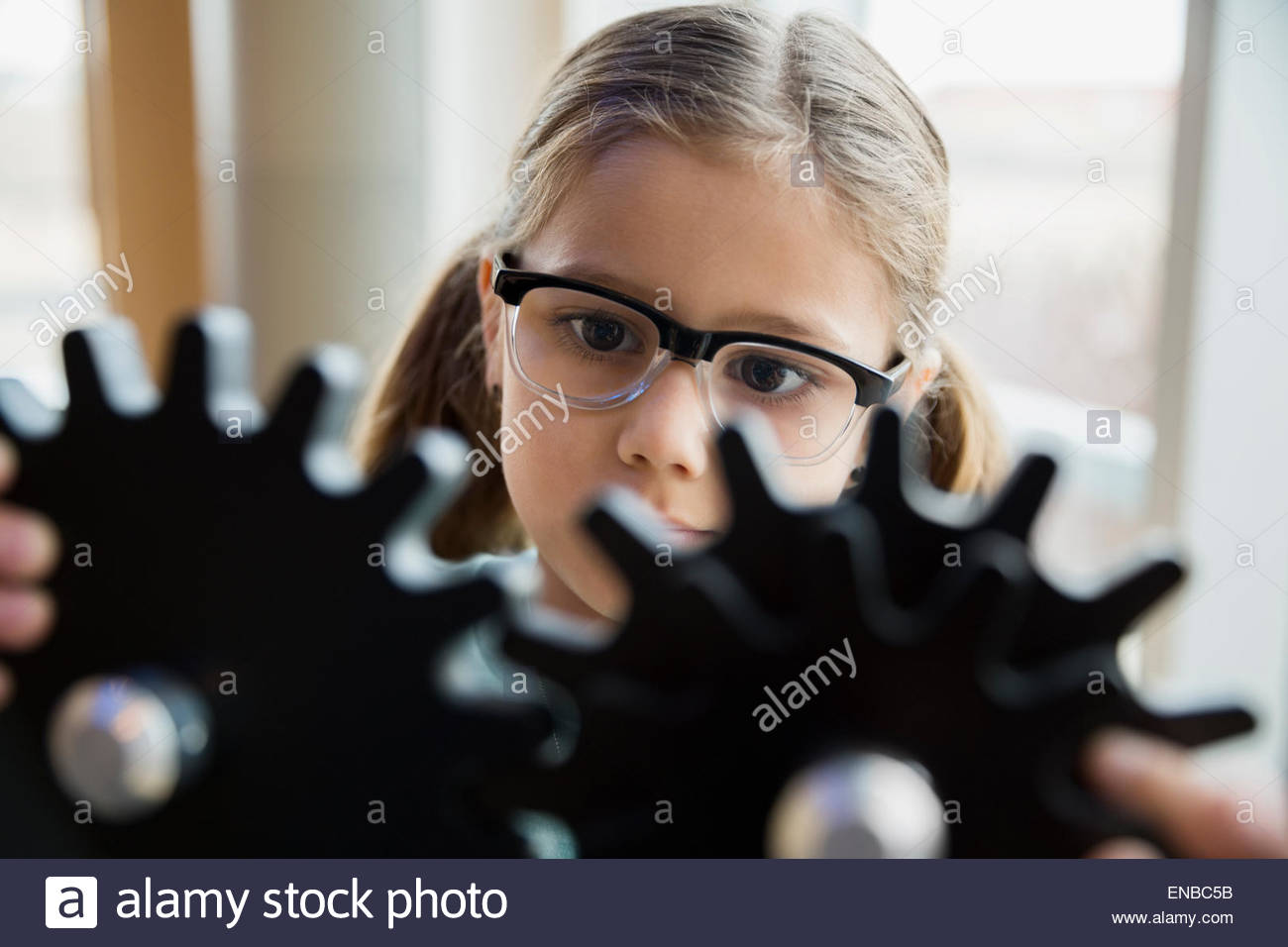 Curious girl examining cog gears at science center - Stock Image