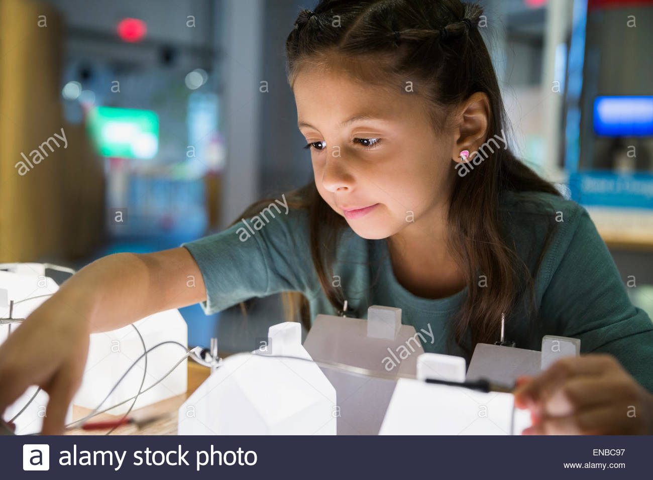 Curious girl playing at electricity grid science center - Stock Image